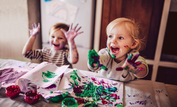 Two children playing with finger-paints, looking excited.