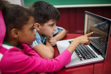 A boy and a girl using the computer together.